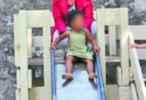 Esther Alder, conseillère administrative, joue avec un enfant sur un tobbogan du parc des Bastions; un jeu bientôt changé.