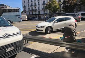Sur la place Dorcière, une voyageuse attend son bus assise sur la glissière de sécurité. DR
