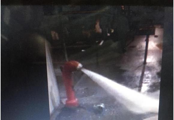 La photo prise le soir par le commerçant (en médaillon) montre la puissance du jet et un tuyau situé à côté de l'hydrante. DR