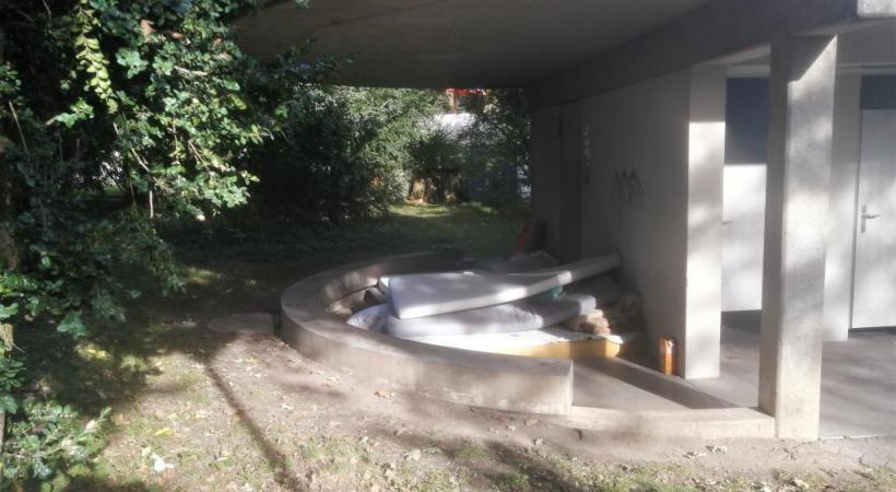 Des matelas entassés sous l'avant-toit des toilettes publiques du parc durant la journée. TR