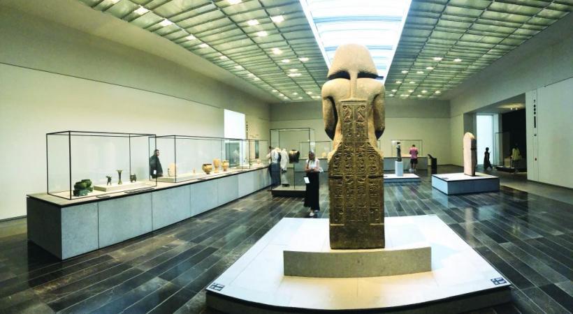 Devant la statue de Ramsès II, une vaste salle montrant un style de présentation aéré.