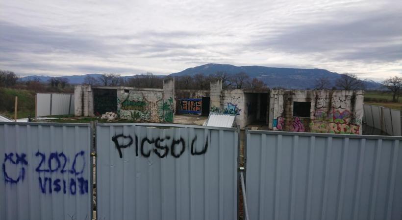 Le bâtiment couvert de tags est entouré de barrières en tôle. MP
